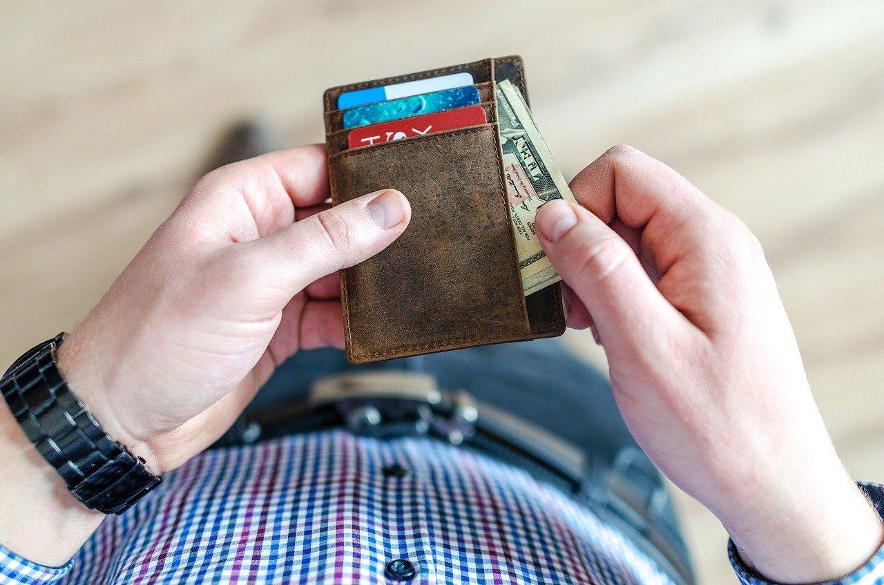 CLASの料金を支払うために財布を取り出す人