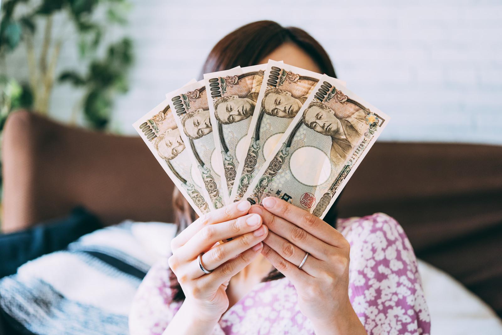 お金を両手で広げる女性